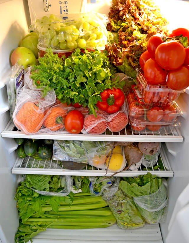 Fruits and vegetables fill a refrigerator