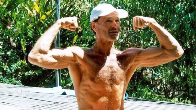 Dr. Doug Graham flexes his biceps outside
