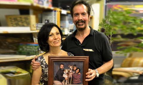 Tim and Leslie Arnold pose with a photograph after the June 2013 potluck at Arnold's Way