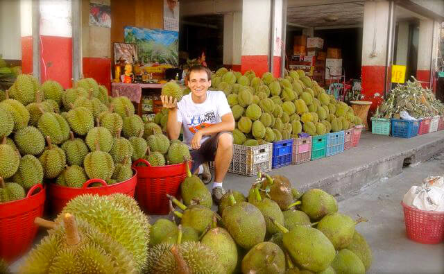 Andrew Perlot holds a durian amid dozens of the tropical fruits