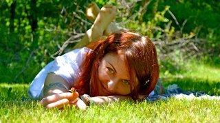 Anna Chmielewska lays on grass, holding a flower