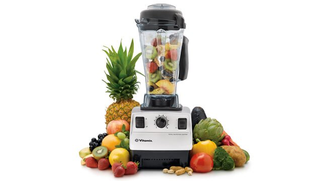 A Vitamix blender surrounded by fruits against a white background