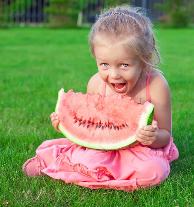 A young girl wearing a pink dress eats watermelon in a field