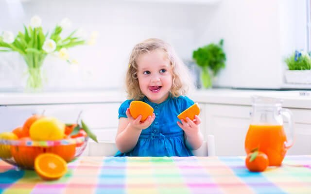 A young girl playfully eats oranges at a kitchen table