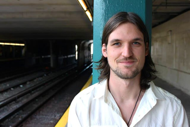 Josh Fossgreen poses at a train station