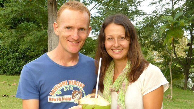 Paul and Yulia Tarbath pose while holding a coconut