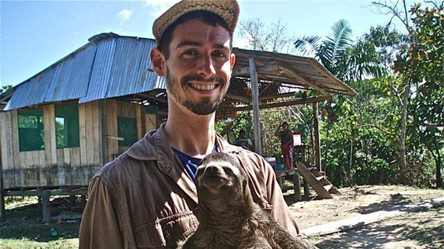 Joshua Duncan holds up an animal in Peru