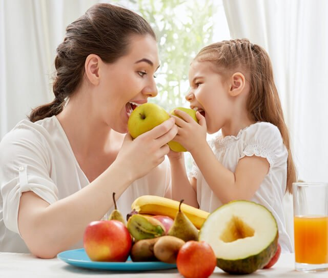 Mother and daughter eat fruits