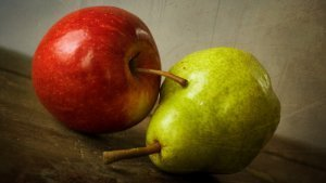 An apple and pear against rustic background