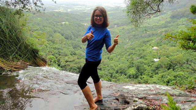 Elisa Oras gives thumbs-up on a mountain