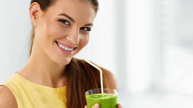 Woman holding a green smoothie with a straw