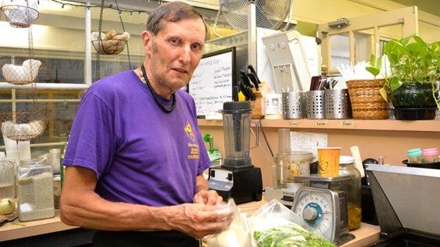 Arnold Kauffman puts on gloves in the Arnold's Way kitchen