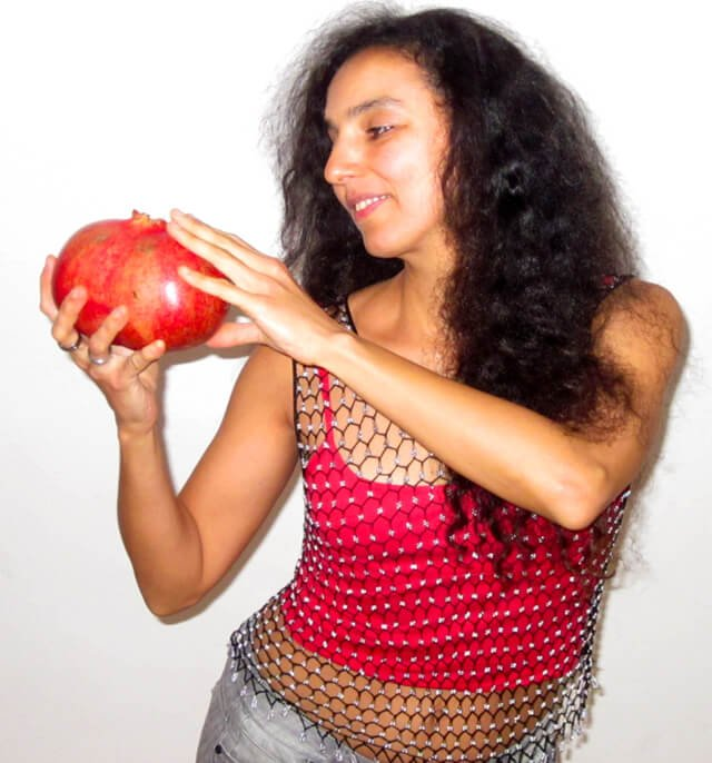 Eva Fruit looks at a large pomegranate she holds