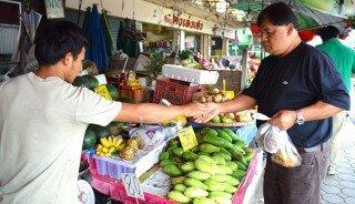 A man purchases fruits at Muang Mai Market in Chiang Mai, Thailand