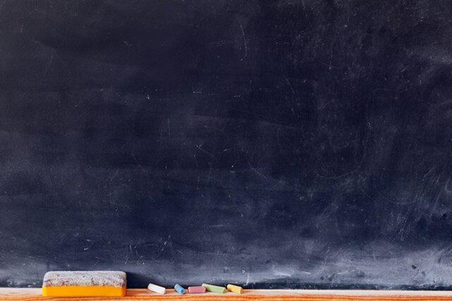 Blank blackboard with colored chalks