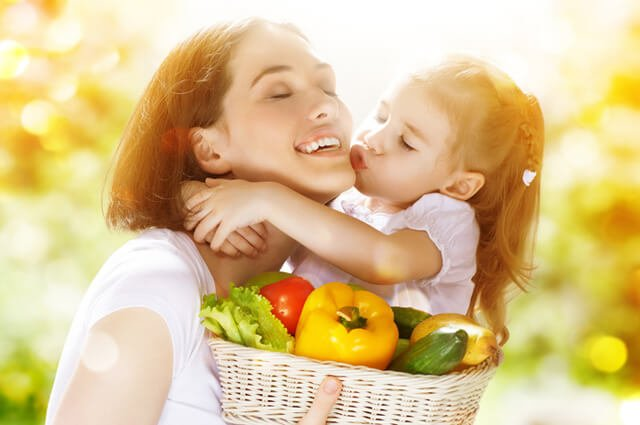 A daughter kisses her mom, holding a basket of fruits and lettuce