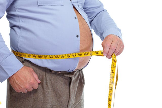 Man measures stomach, bursting through a shirt