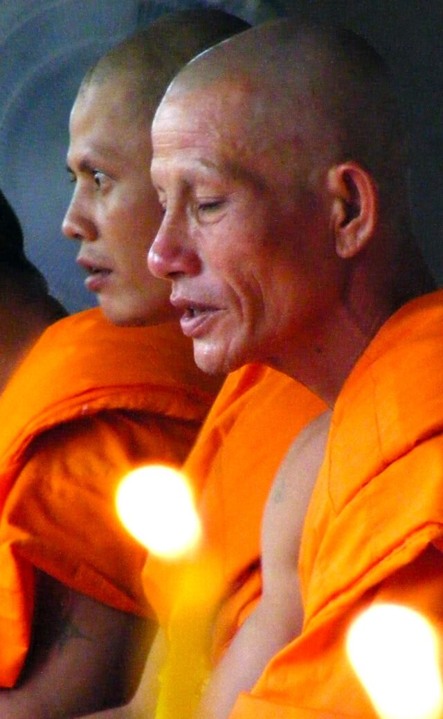 Buddhist monks meditate wearing orange robes