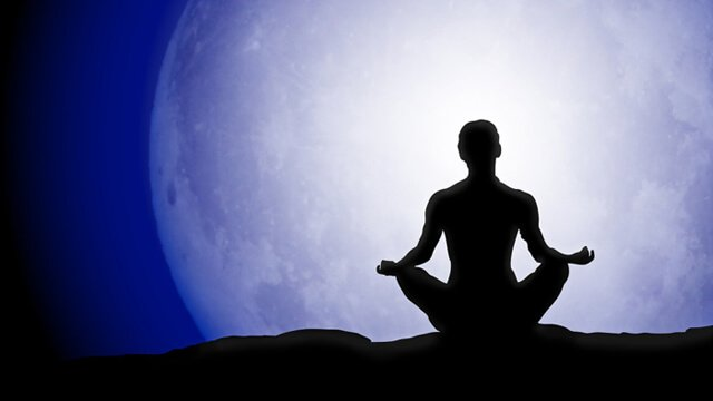 Silhouette of a man meditating beneath a full moon