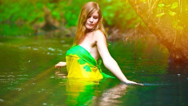 A woman with a yellow-and-green dress wades into a lake