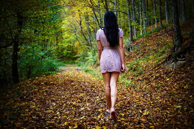 A woman walks barefoot in the woods in autumn
