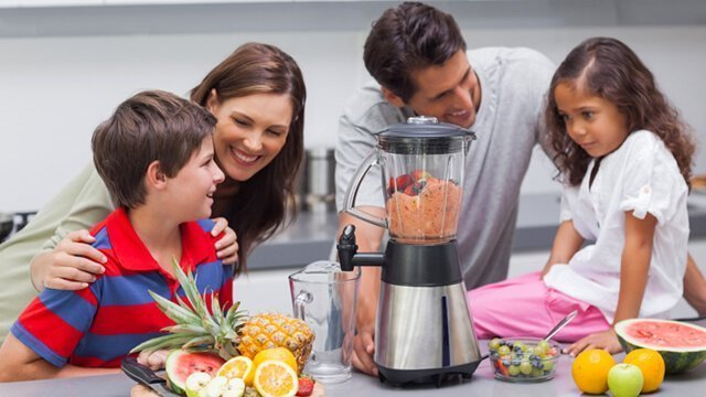 A family gathers around a blender to make fruit smoothies