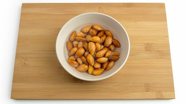 Almonds soak in water in a bowl on a wooden surface