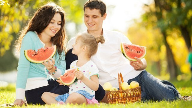 A small family enjoys eating watermelon in a park