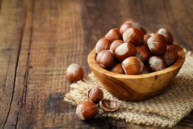Hazelnuts overflowing from a wooden bowl