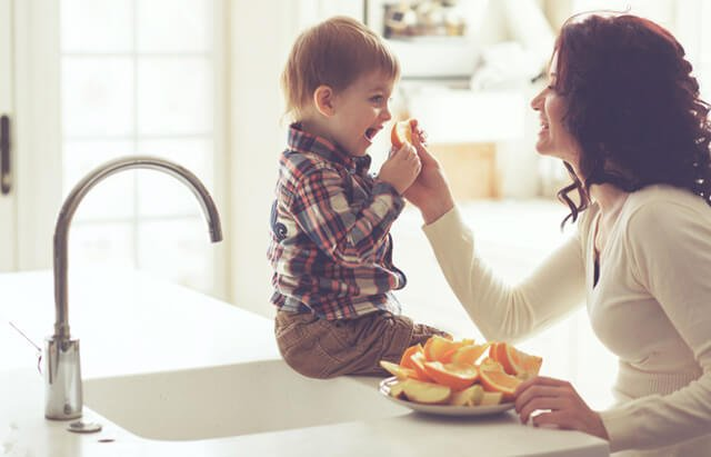 A mother feeds her young boy oranges by a kitchen sink