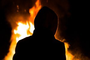 The back of a hooded man at a bonfire