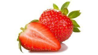 Strawberries whole and cut on a white background