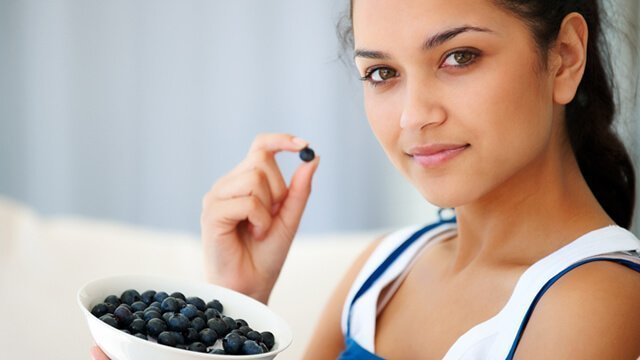 Young woman eating from a bowl of blueberries