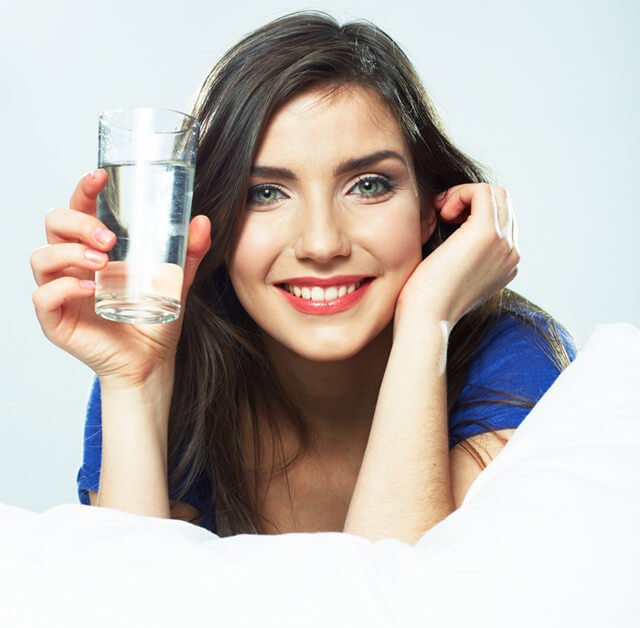 Woman holds a clear glass of water