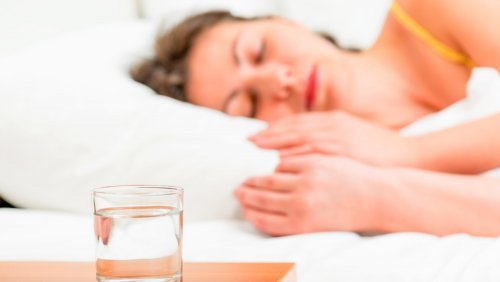 Water fasting - woman sleeping with glass of water at bedside - Fruit-Powered