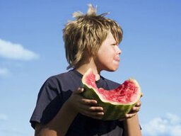 A boy enjoys eating watermelon outdoors