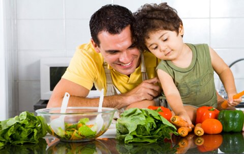 A father shows his son how to prepare salad