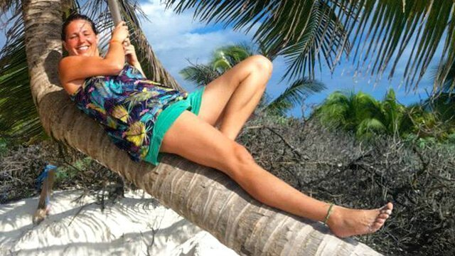 Melanie Lotos lounging on a palm tree