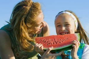 Mom and daughter enjoy eating watermelon outdoors