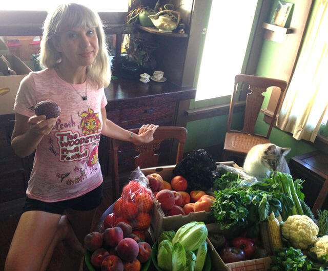 Anji Bee of Happy Healthy Vegan photographed with a large quantity of fruits and vegetables