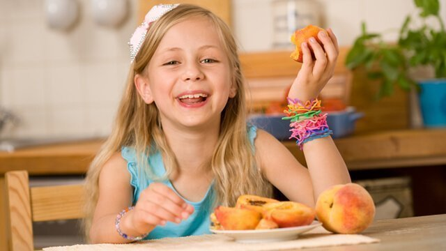 A girl eating peaches from a plate