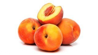 Four peaches whole and halved against white background