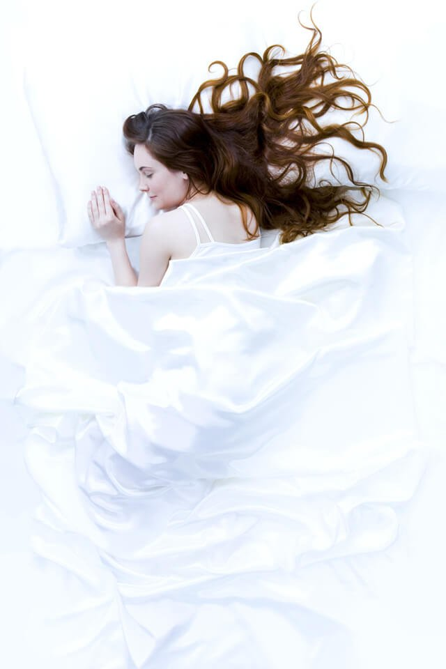 A woman sleeping in bed, covered with white sheets