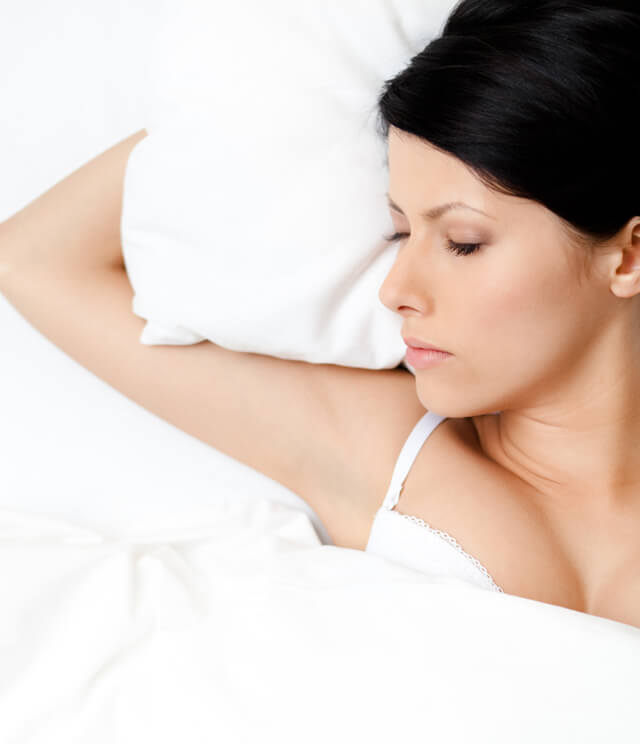 Woman asleep in bed under white covers