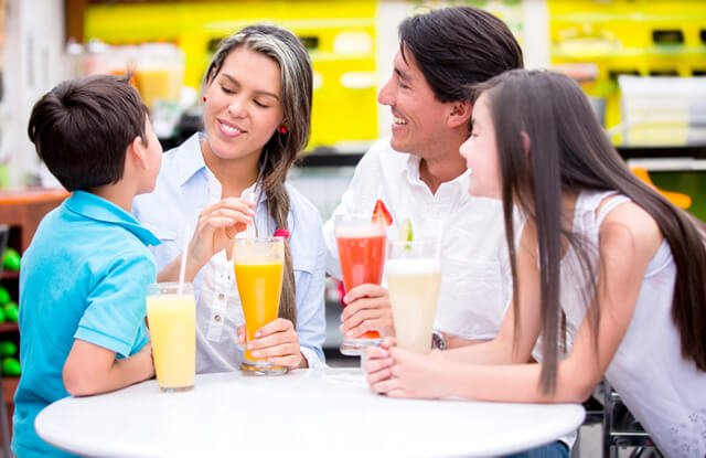 A family drinks smoothies while gathered around a table