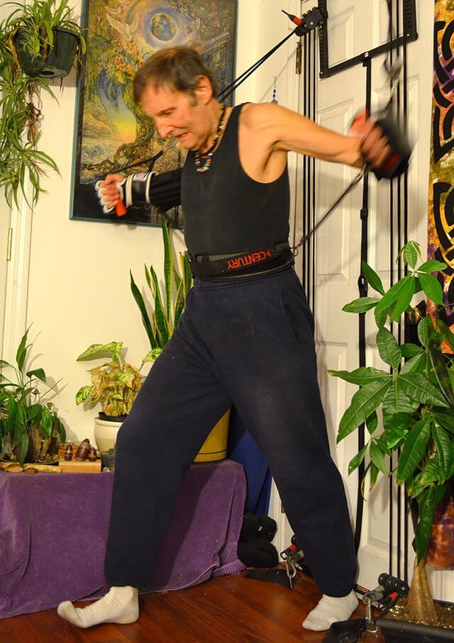 Arnold Kauffman exercises using resistance bands secured against a door