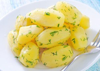 Peeled and cooked potatoes on a white plate