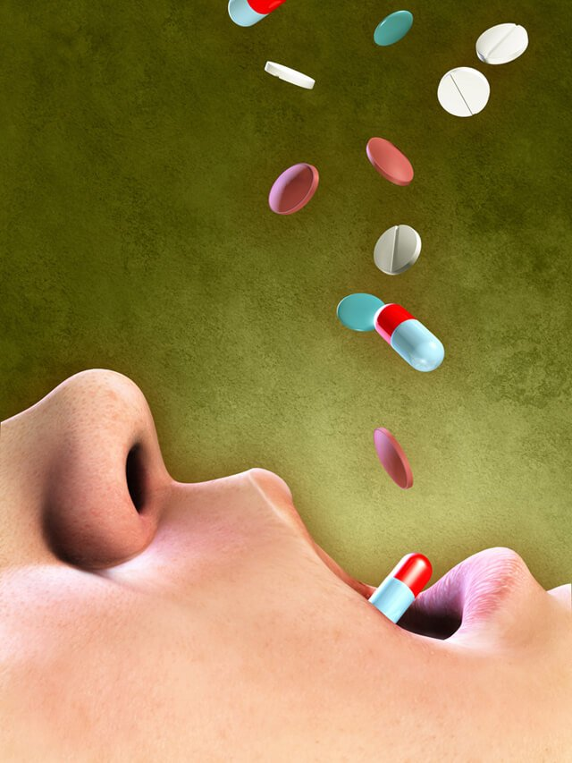 Pills falling into an open mouth
