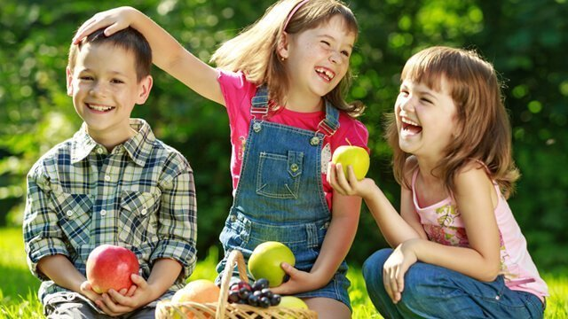 Two girls and one boy play outside while eating from a basket of fruit