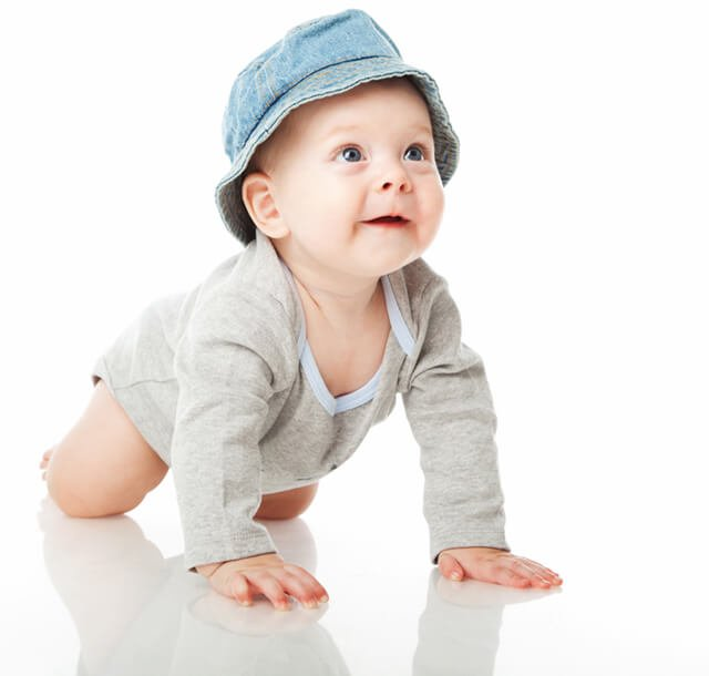 A baby boy crawls in a white studio
